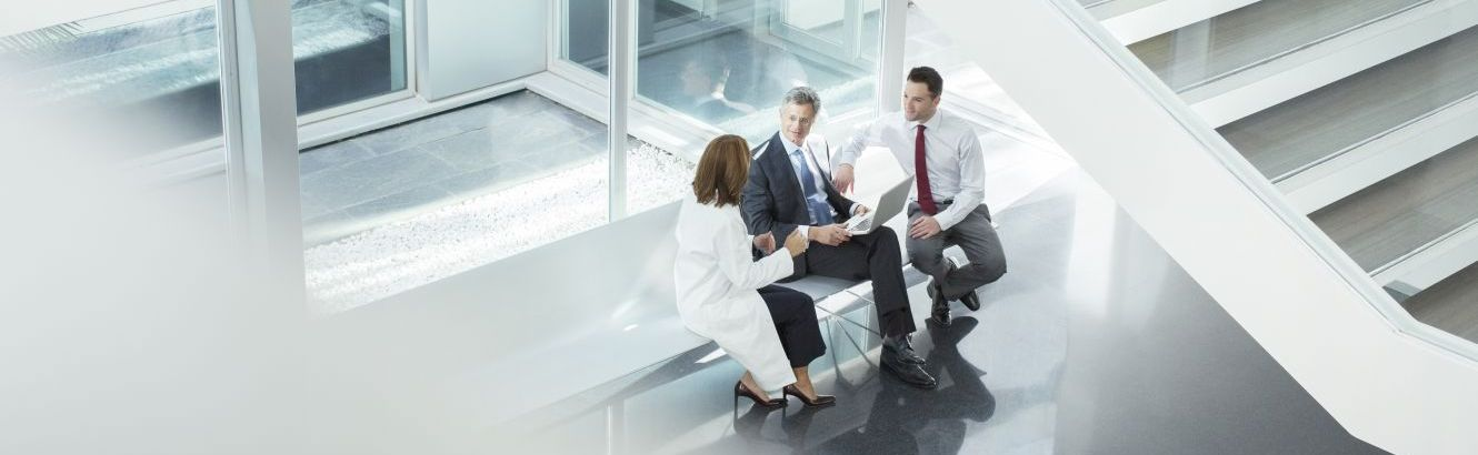 A small group of business professionals meeting by stairs